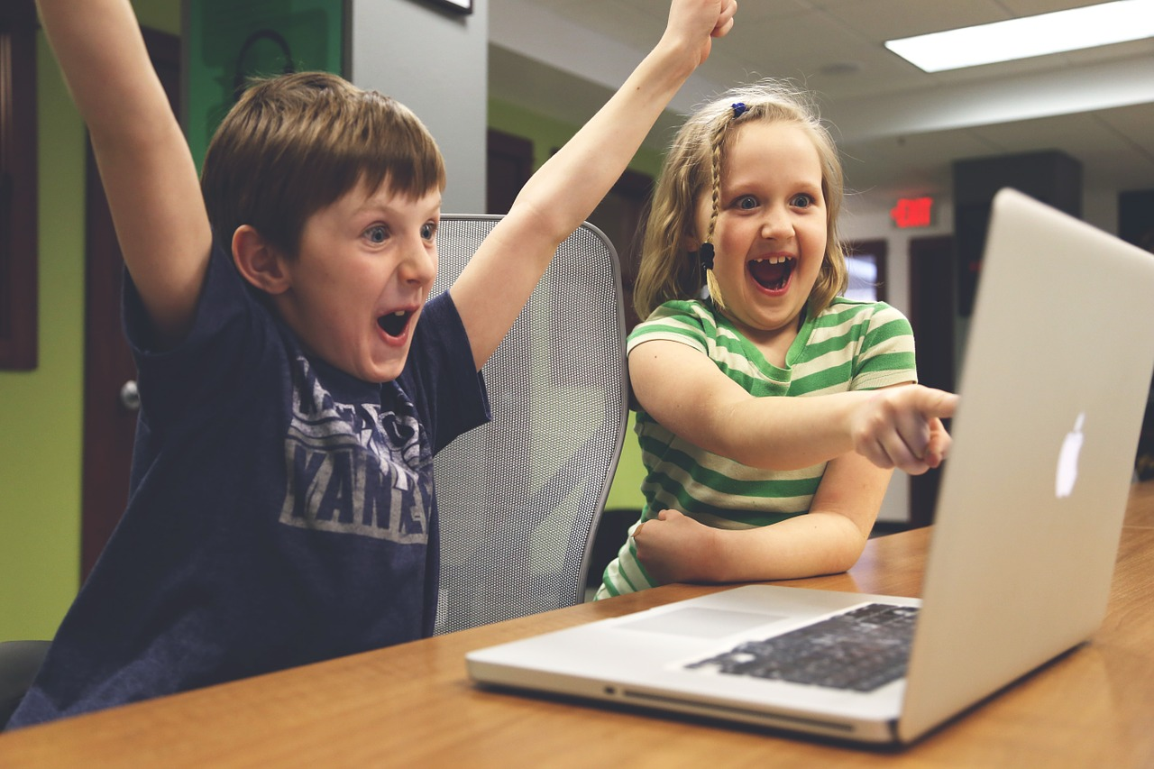 Children excited in front of a computer