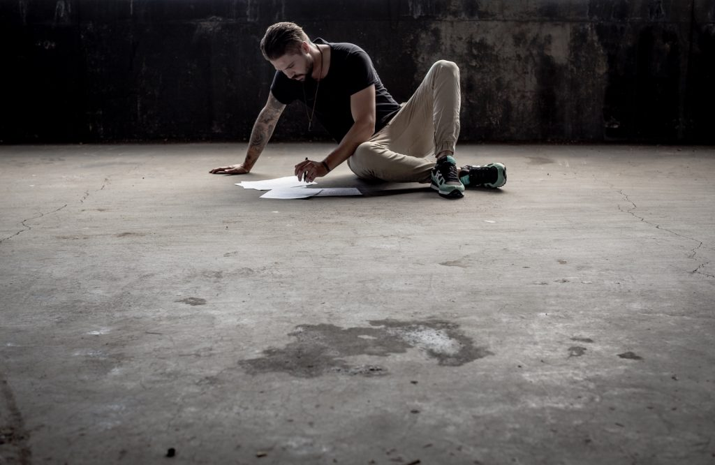 man writing in empty room